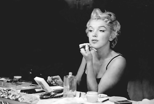 Marilyn_Monroe_putting_on_her_makeup_with_makeup_and_perfume_in_front_of_her_.jpg